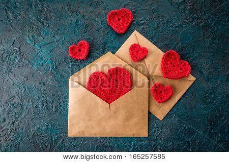 Crochet valentine hearts and envelope on dark bacground.