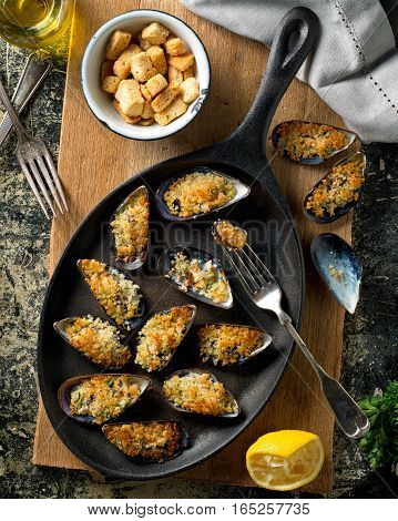 Delicious baked mussels on an iron skillet with breadcrumbs lemon parsley garlic and olive oil.