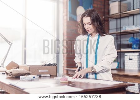 Pretty young fashion designer cutting cloth using scissors while working in studio.