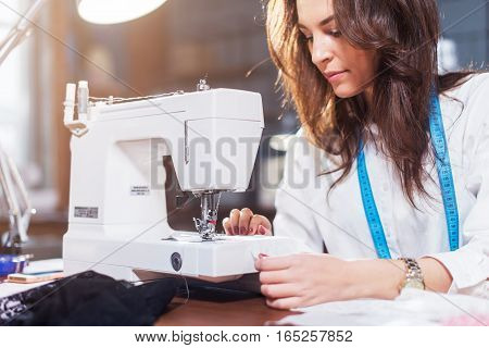 Young female fashion designer working on sewing machine in a workshop.