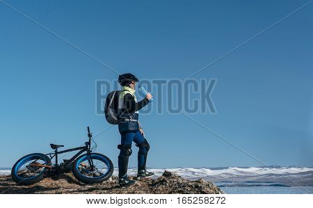 Cyclist drinks water from a bottle while relaxing. Fatbike also called fat bike or fat-tire bike - Cycling on large tire wheels. Cyclist goes to his bike on the frozen lake.