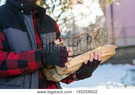 Man Carrying Firewood In The Yard