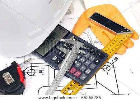 Helmet, calculator, rule, glove and vernier caliper on a technical drawing