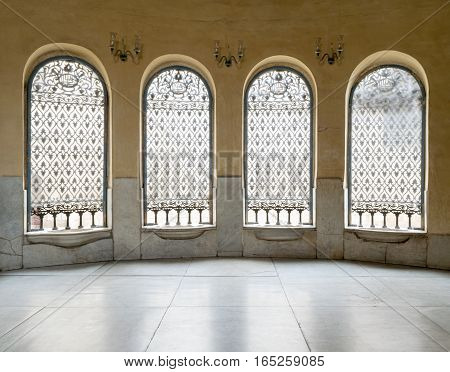 Windows with iron decorated grid, yellow wall, and marble floor
