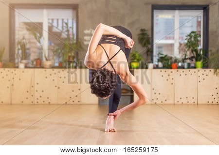 Woman doing yoga, exercising, training in gym stretching bending forward standing on one leg.