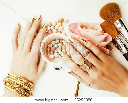 woman hands with golden manicure and many rings holding brushes, makeup artist stuff stylish, pure beauty close up