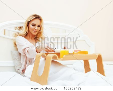 young beauty blond woman having breakfast in bed early sunny morning, princess house interior room, lifestyle people concept
