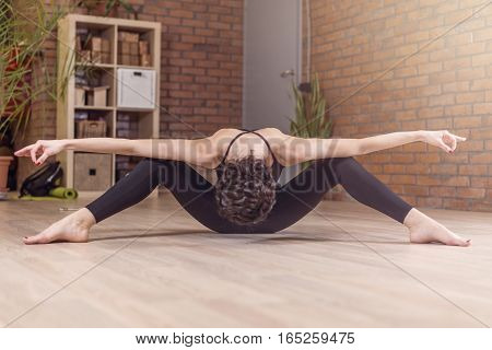 Professional dancer sitting facedown stretching with her legs spread and arms outstretched posing in artistic posture in studio.