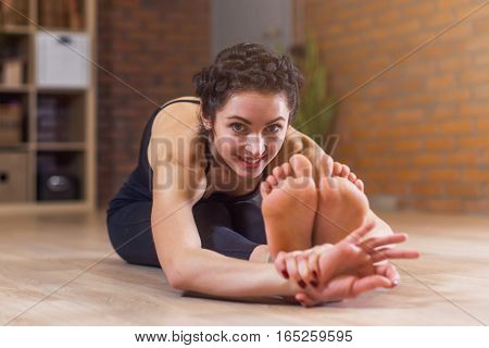 Pretty European woman sitting barefoot stretching her back and legs sitting on floor bending forward looking at camera
