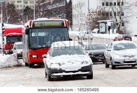 Solna Sweden - January 4 2017: Snowy vehicles with hidden license plates on street Frosundaleden towards Solna city center at the junction with the street Ankdammsgatan.