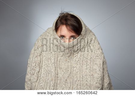 Girl pulls a large knitted sweater over her head. Despair and loneliness of depressed person