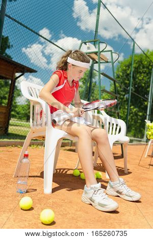 Young female tennis player on break, toned image
