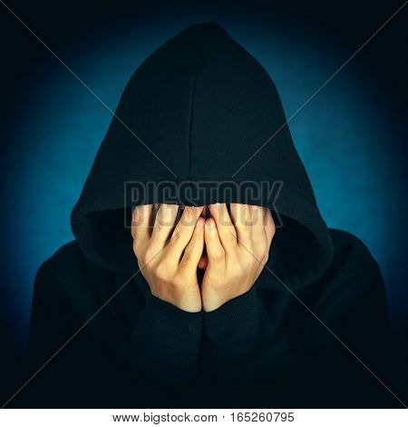 Toned Photo of Sad Man in the Hood on the Dark Background