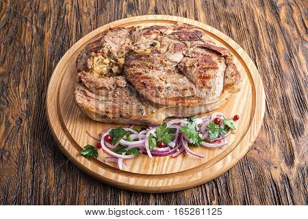Medium rare grilled Beef steak Ribeye with onion on cutting board on dark wooden background. Top view
