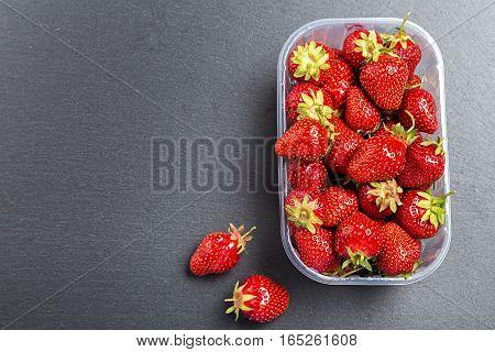 fresh strawberries in plastic box on a slate board top view