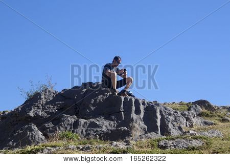 guy making contact with others with his mobile in the mountain