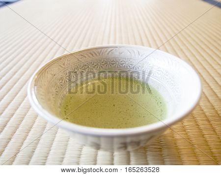 Traditional Japanese green matcha tea served on a tatami mat.