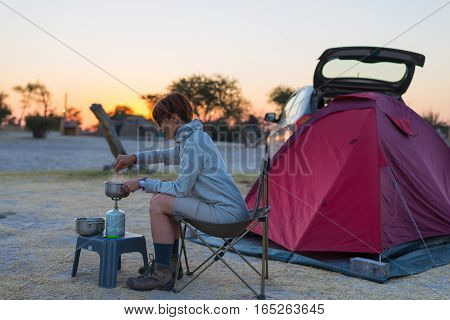 Woman cooking with gas stove in camping site at dusk. Gas burner pot and smoke from boiling water tent in the background. Adventures in african national parks.