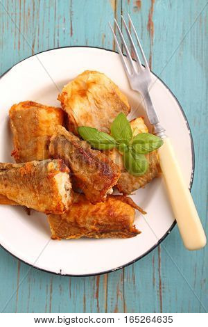 fried hake fish in a white plate