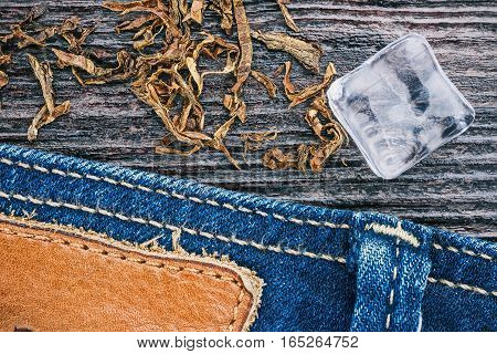 Blue jeans stitched edge, tobacco flakes and ice cube on wood. Macro view and Macro view and Macro view