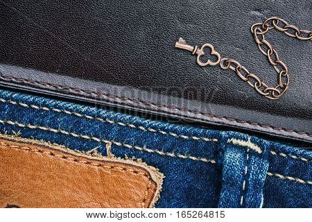 Blue jeans stitched edge and dark brown leather combined background with copper chains and little key. Macro view