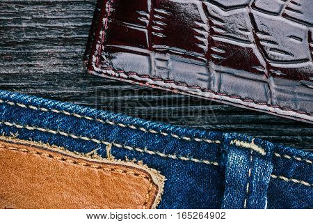 Blue jeans stitched edge, dark wood and reptile leather corner combined background. Macro view