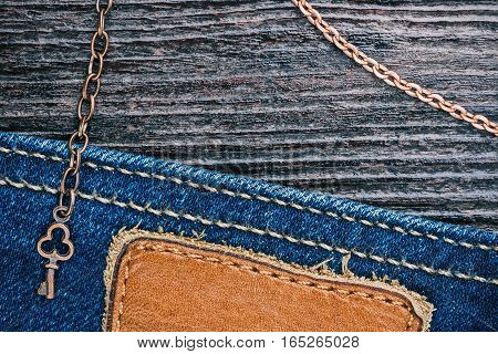 Blue jeans stitched edge and dark brown wood combined background with copper chains and little key. Macro view