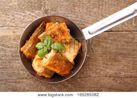 fried fish hake in a frying pan decorated with basil