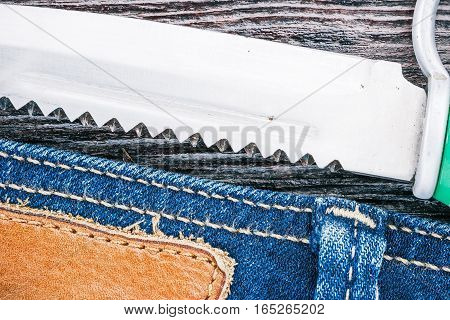Blue jeans stitched edge and knife on dark wood. Macro view