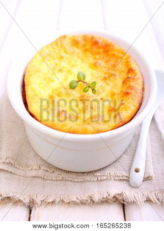 Cottage cheese casserole in white dish decorated with mint on a white wooden background. Selective focus.