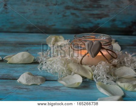 Composition of spa treatment rose, candle on wooden background. Copy space.