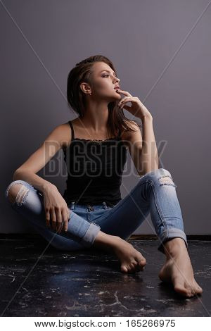 Young sexy woman posing in blue ripped jeans and black lace top sitting on the floor studio shot