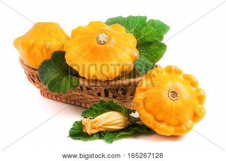 yellow pattypan squash with leaf and flower in a wicker basket isolated on white background.