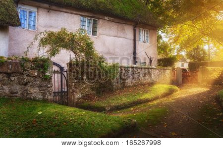 Courtyard at the old two-storey house. Evening. Autumn. A ray of sunshine breaking through leaves. Chagford. Dartmoor. Devon. UK