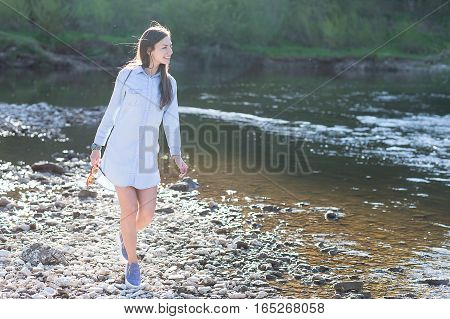 beautiful young woman walking on rocks next to the river in the summer forest background. think and dream concept.