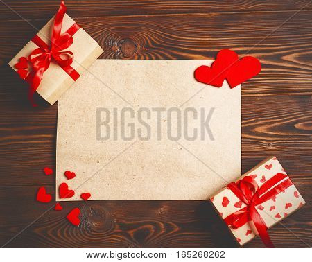 Card to Valentine's day. blank empty paper sheet and a red heart on a wooden background