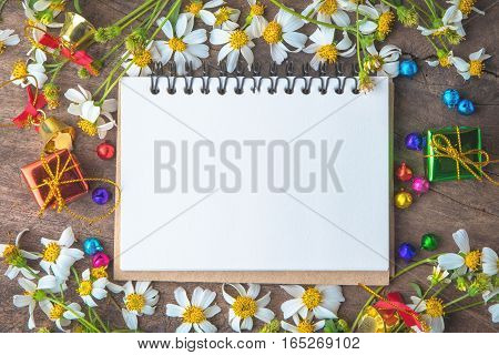 Christmas and new year wooden background banner with blank notebook gift box daisy flower candy ball and decoration on vintage background.