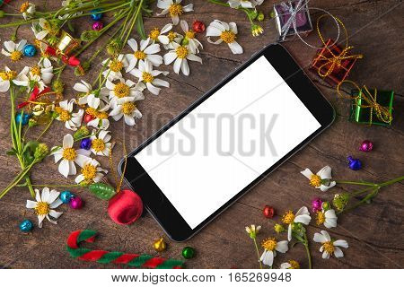Christmas and new year wooden background banner with blank smart phone gift box daisy flower candy ball and decoration on vintage wooden background.