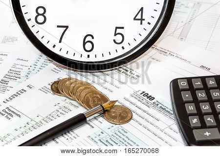 Calculator clock coins and pen on tax form 1040. Bosiness concept.
