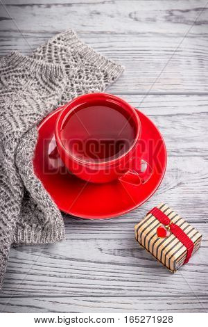 Cup of tea, knitted mitts and a gift for Valentine's Day on the gray wooden background