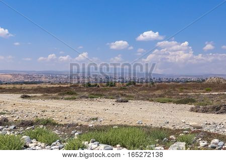 Landscape view of Lady's Mile in Limassol, Cyprus.  Taken in the summer and shows dried up lake bed with misty urban view and mountains in the background.