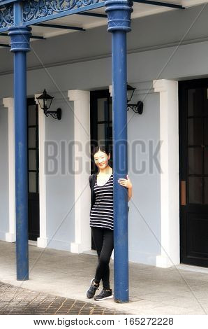 A chinese womna smiling leaning against a metal pole in the city of macau china at fisherman's wharf.