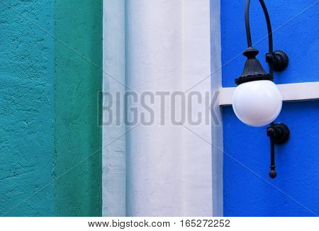 A wall of three different colors with a single mounted wall light within the fishermans wharf area of macao china.