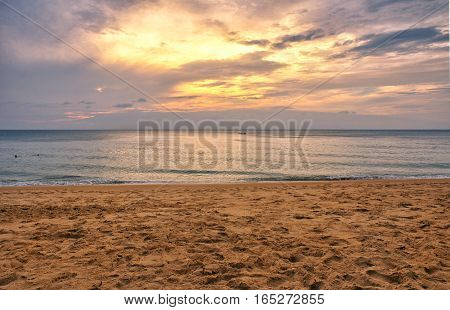 The sands of Mai khao beach in Talang city on Phuket Island thailand overlooking the andaman sea at sunset.