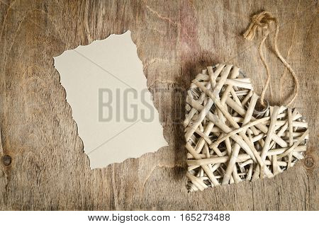 wicker heart handmade lying on a wooden base with a sheet of paper
