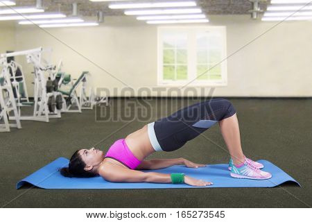 Pretty young woman doing yoga exercise in the fitness center and practicing the bridge pose on the mattress