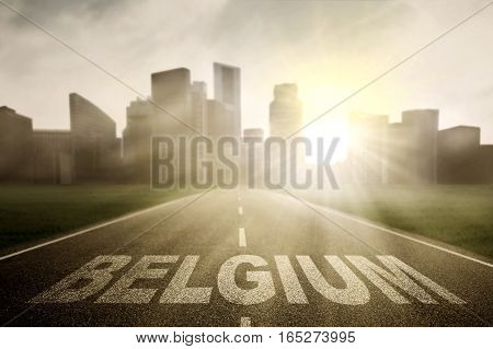 Image of empty road with word of Belgium and bright sunlight toward a town