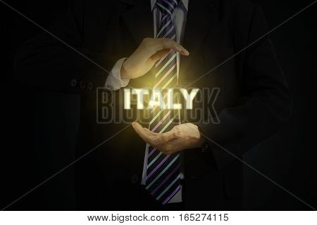 Image of businessman wearing formal suit while holding a bright word of Italy on his hands