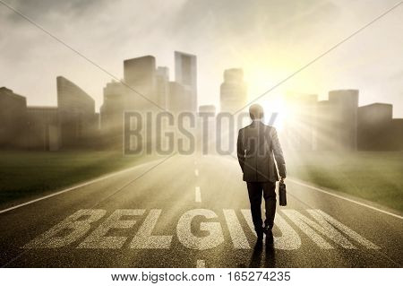 Businessman walking on the street while carrying a briefcase with Belgium word shot in the morning
