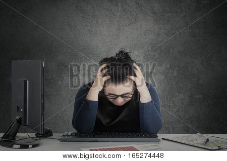 Businesswoman holding her head on the desk while feeling dizzy with financial crisis